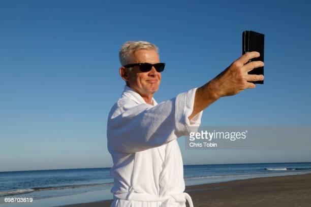 Man in bathrobe taking selfie on beach