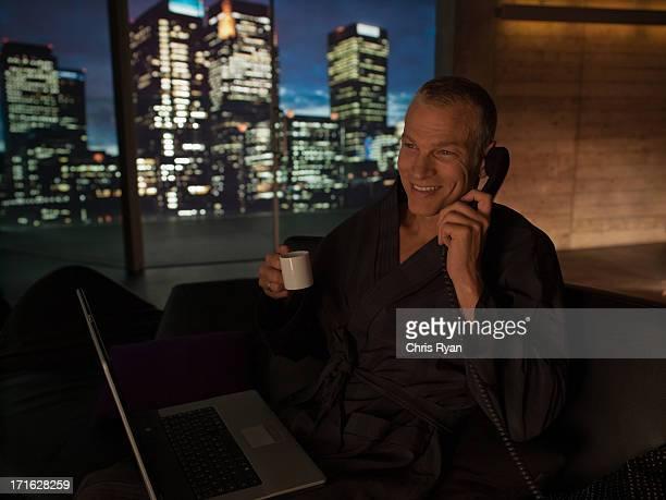 Homme dans un peignoir avec ordinateur portable, boire du café et de parler