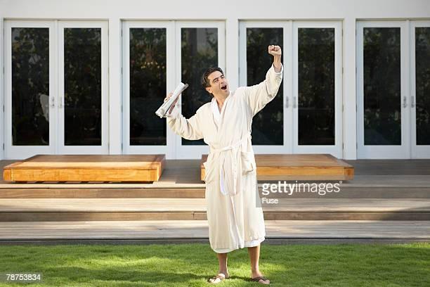 Man in Bathrobe Yawning, Stretching and Getting Morning Newspaper
