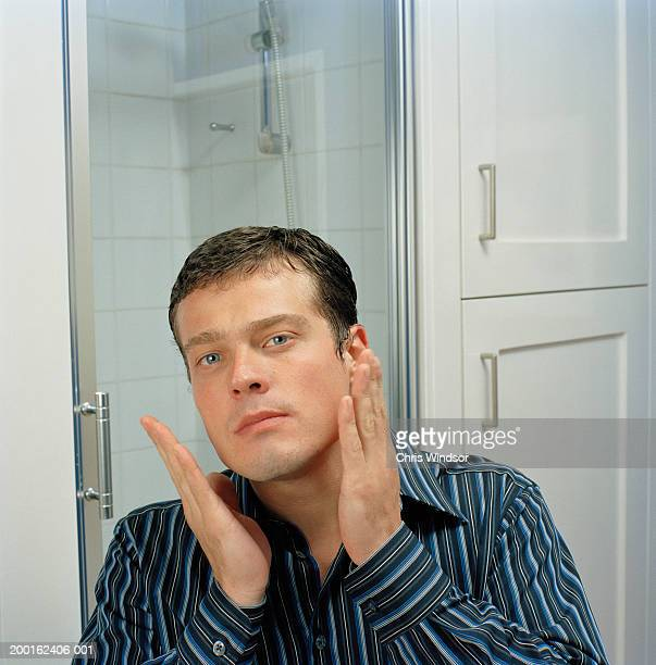 Man in bathroom applying aftershave, portrait