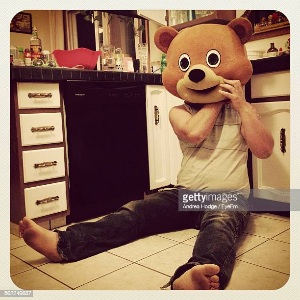 man in bear costume relaxing on floor in kitchen - animal costume stock pictures, royalty-free photos & images