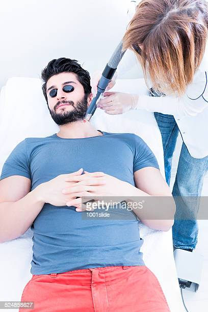 man in beauty spa - laser epilation - medical laser stock photos and pictures