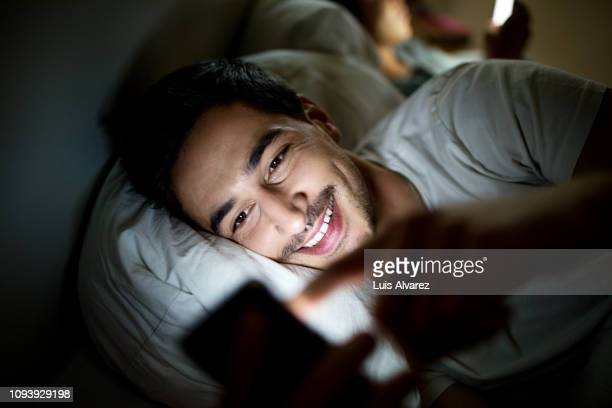 man in bed checking his social media status on smartphone - bed stock pictures, royalty-free photos & images