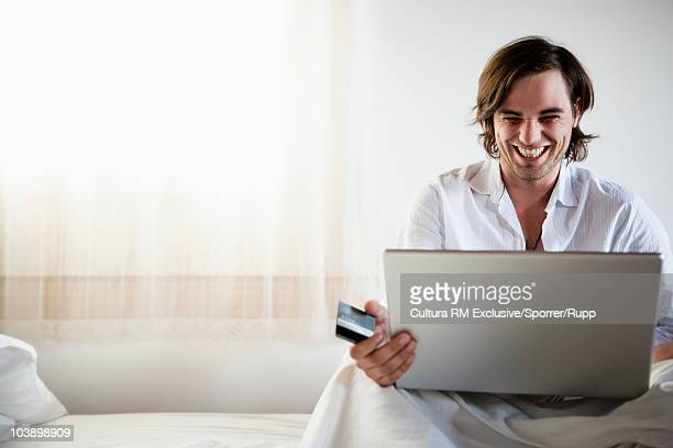 Man in bed shopping online