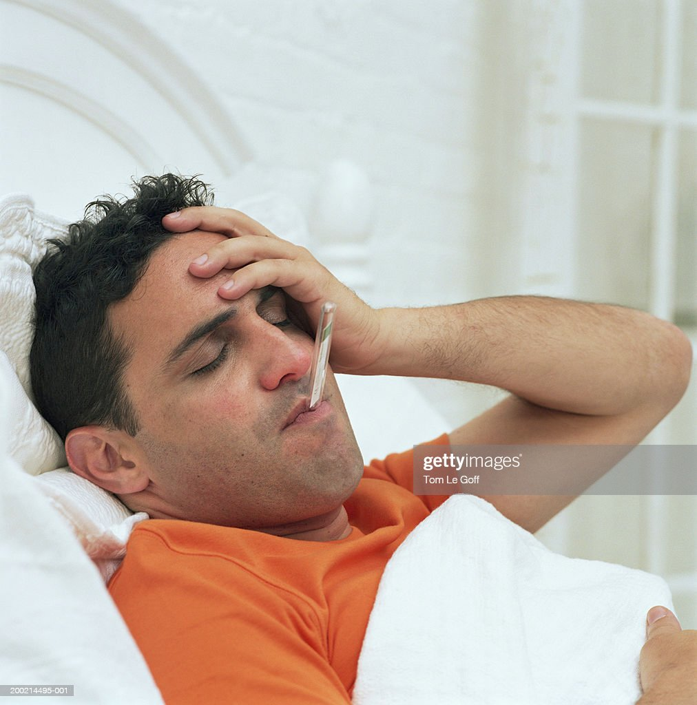 Man in bed with thermometer in mouth, holding head, eyes closed : Stock Photo