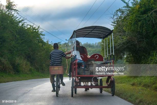 Man in bicycle holding a horsedrawn carriage on a rural road Cuban transportation scene