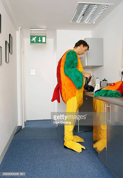 Man in bird costume pouring water from kettle into mug