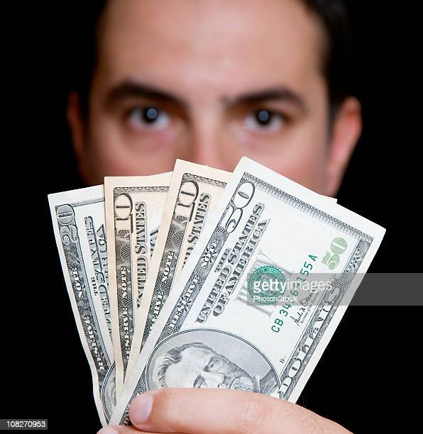 man in black hides behind money
