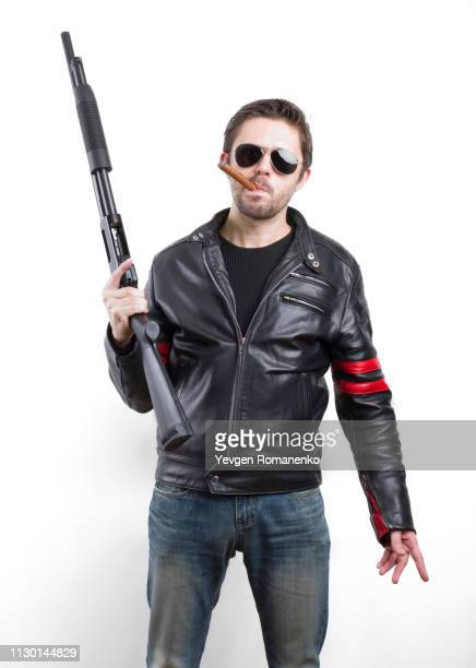 man in black leather jacket and sunglasses with gun - shotgun stock pictures, royalty-free photos & images