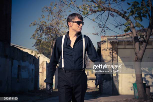 man in black shirt looking away while walking outdoors. - zwart shirt stockfoto's en -beelden