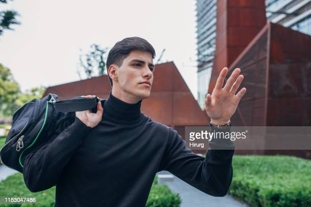 man in black turtleneck catching taxi - turtleneck stock pictures, royalty-free photos & images