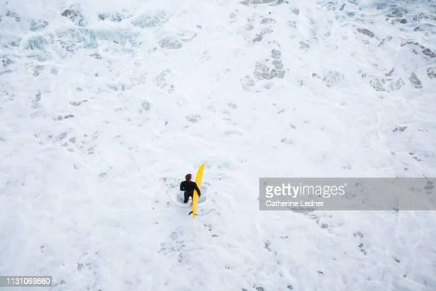 Man in black wet suit holding yellow surfboard in foamy water