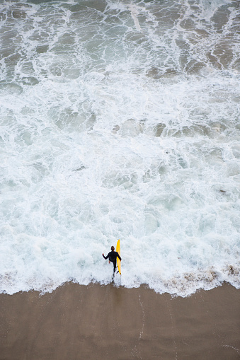 man in black wetsuit running into ocean from above holding yellow surfboard - gettyimageskorea