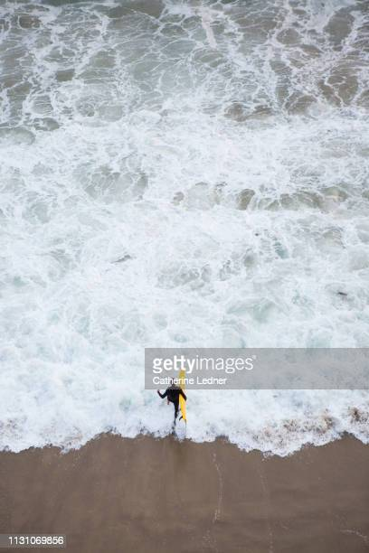 man in black wetsuit running into ocean from above holding yellow surfboard