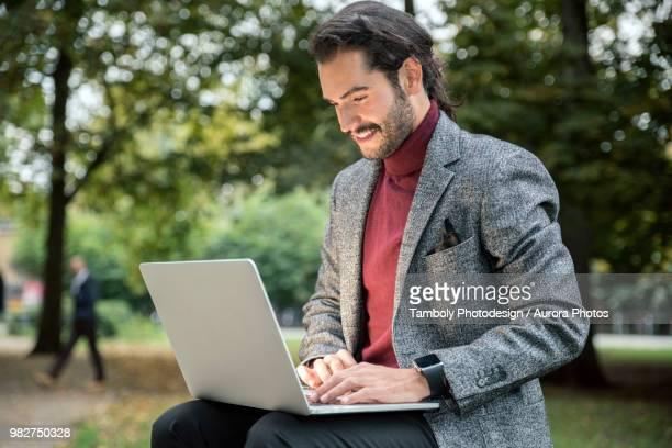 man in blazer using laptop in park - businesswear ストックフォトと画像