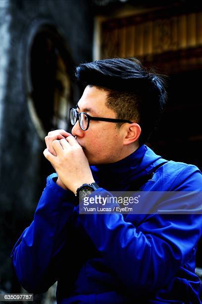 Man In Blue Jacket Playing Harmonica At Event
