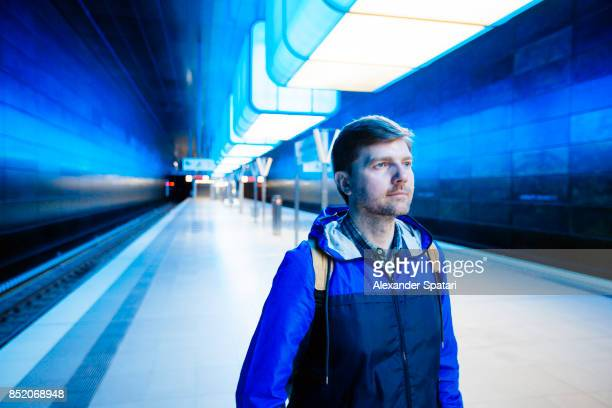 Man in blue jacket standing on a subway station with blue lighting
