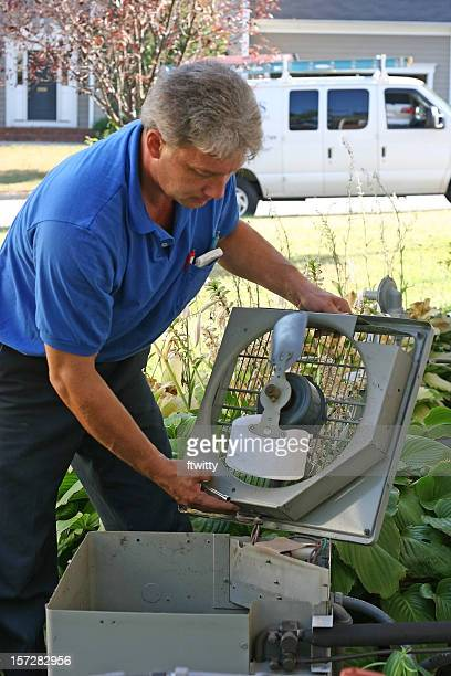 Man in blue shirt with gray hair repairing an AC outdoors