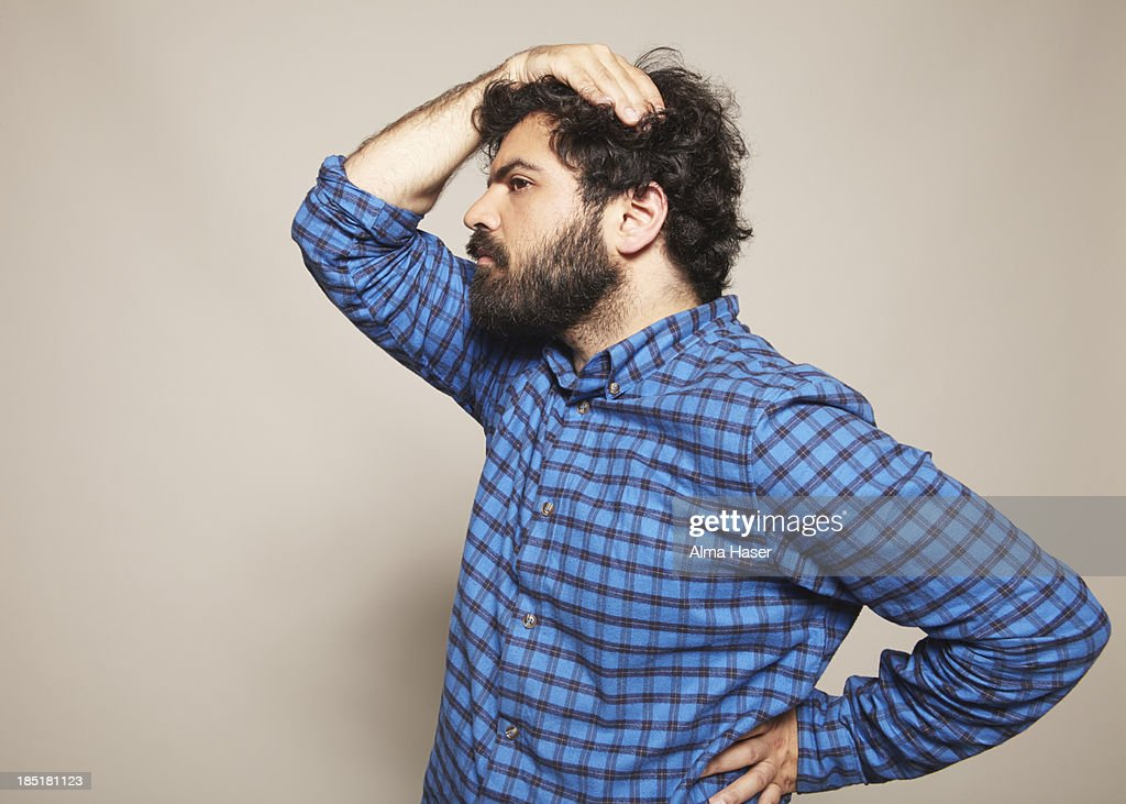 Man in blue shirt with hand on head and hip : Stock Photo