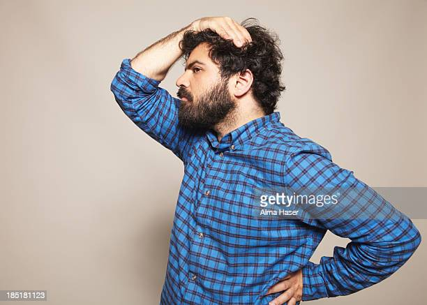 man in blue shirt with hand on head and hip - uncertainty stock pictures, royalty-free photos & images
