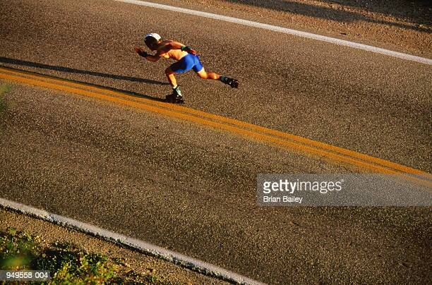 Man in blue shorts and helmet in-line skating on road