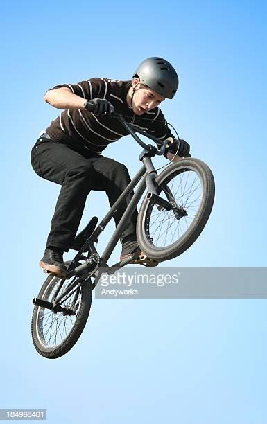 Man in BMX acrobatic action wearing a helmet