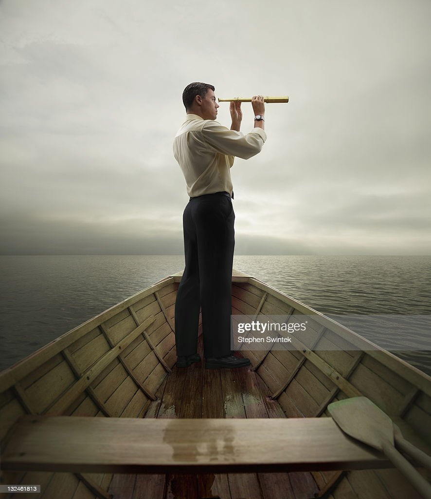 Man in boat looking through spyglass : Stock Photo