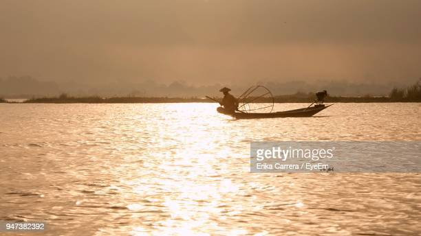 man in boat on lake against sky during sunset - asia carrera stock photos and pictures