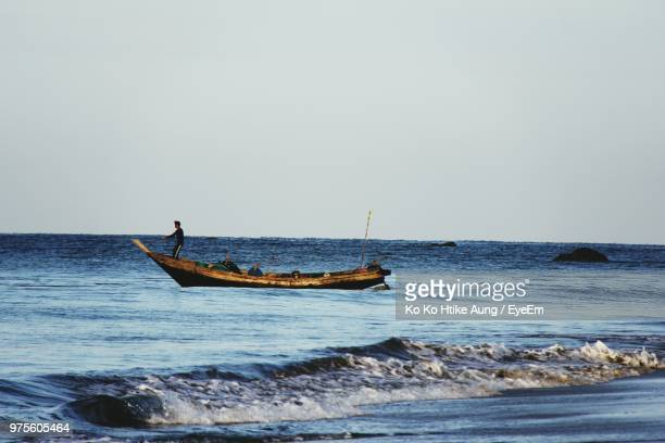 man in boat on sea against clear sky - ko ko htike aung stock pictures, royalty-free photos & images
