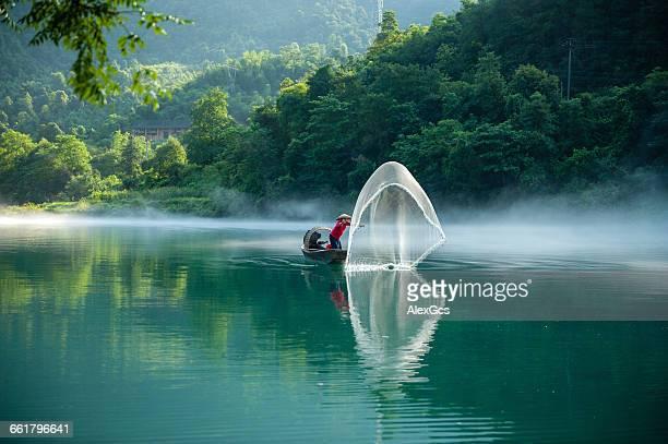 Man in boat throwing fishing net, Chenzhou, Hunan, China