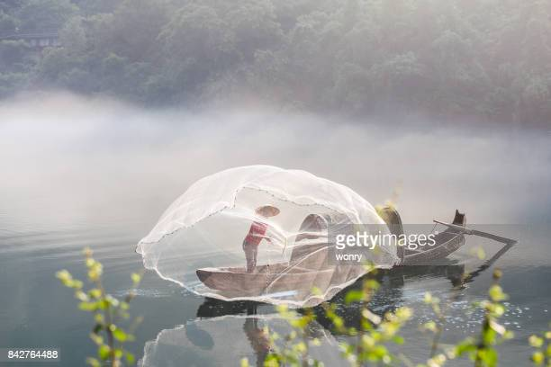 Man in boat throwing fishing net
