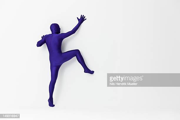 man in bodysuit scaling wall - bodysuit stock pictures, royalty-free photos & images
