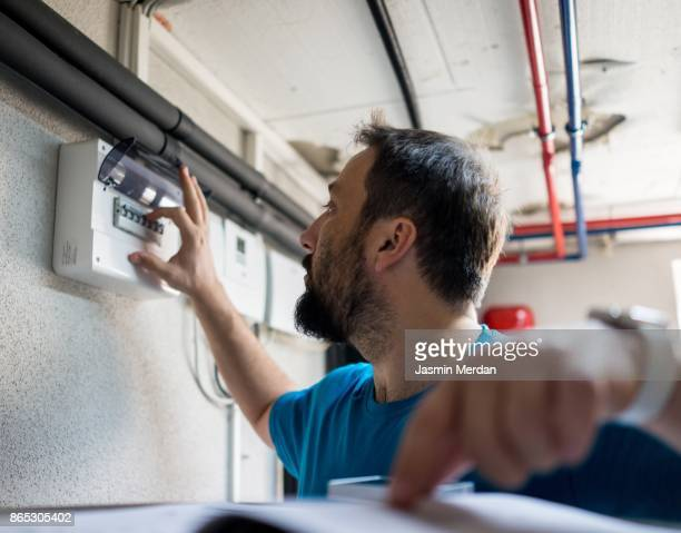 Man in boiler and heating room using control device display for smart home