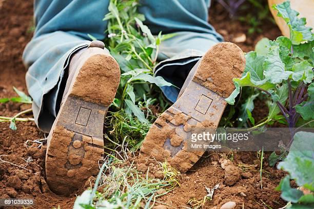 Man in boots kneeling in soil.
