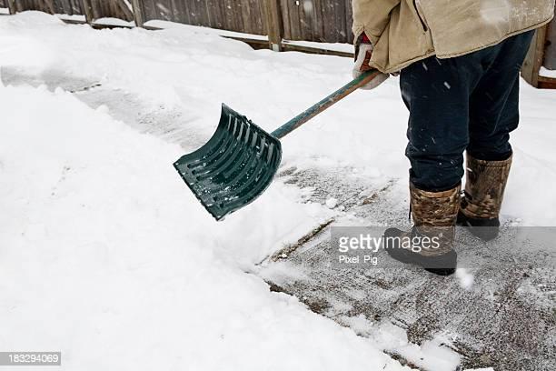 男性のブーツで雪 shoveling から歩道