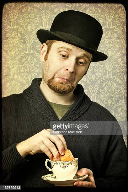 Man in bowler hat with tea and cake
