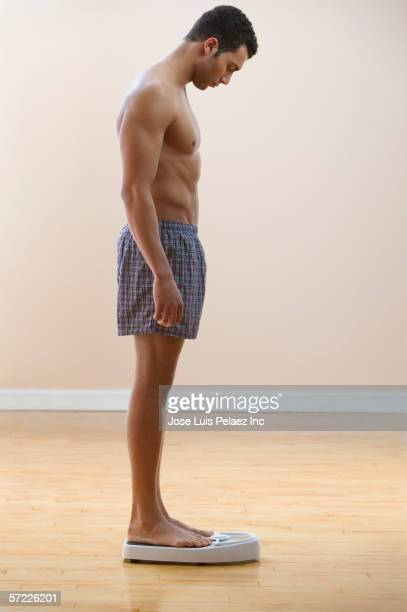 man in boxers standing on scale - boxershort stock pictures, royalty-free photos & images