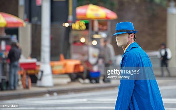 CONTENT] man in bright blue trench coat and blue fedora wearing a mask that blocks the features of his face crossing the road with food carts in the...