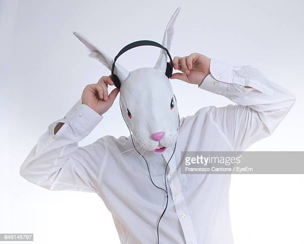 Man In Bunny Face Wearing Headphones Against White Background