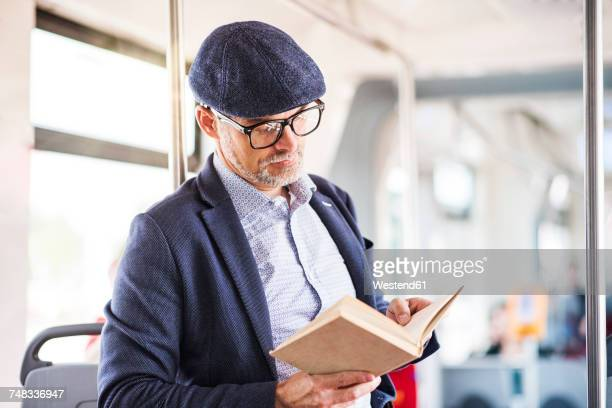 Man in bus reading book