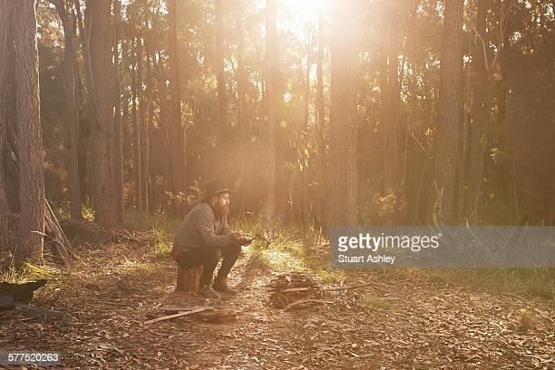 Man in bushland sitting around campfire