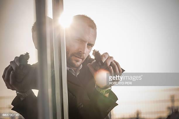 Man in business attire behind corner at harbour poised with handgun, Cagliari, Sardinia, Italy