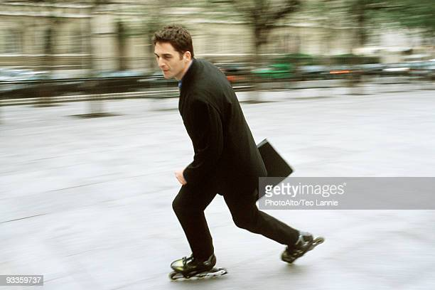 Man in business attire inline skating carrying briefcase in city square