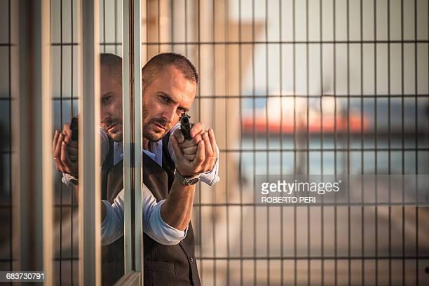 Man in business attire poised behind corner in harbour pointing handgun, Cagliari, Sardinia, Italy