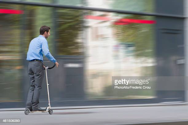 Man in business attire riding on push scooter
