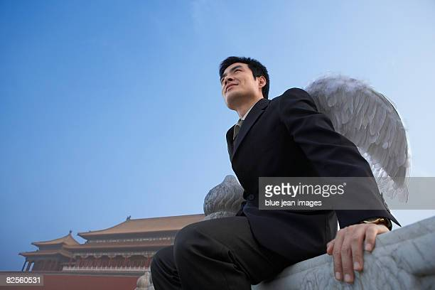 A man in business attire with wings, looks into the distance, Chinese architectural elements behind.
