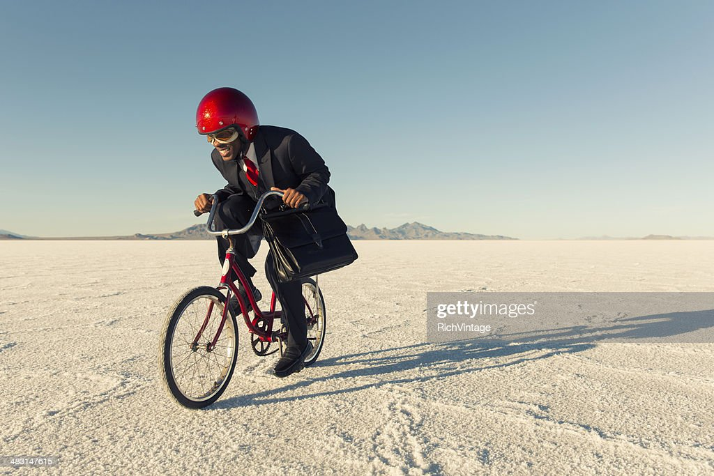 Man in Business Suit and Racing Helmet Races his Bicycle : Stock Photo