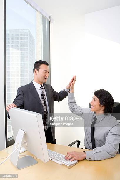 Man in business suit high-fives young employee who is using a computer