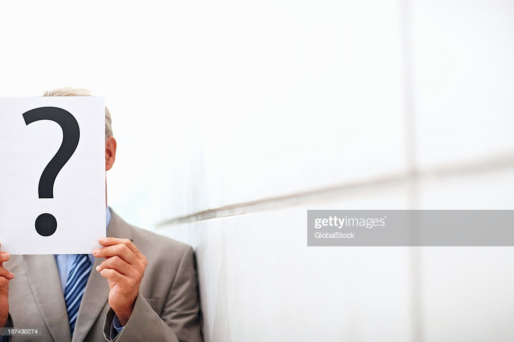 Man in business suit holding question mark sign : Stock Photo