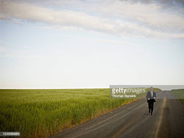 man in business suit running down rural road - rushing the field stock pictures, royalty-free photos & images